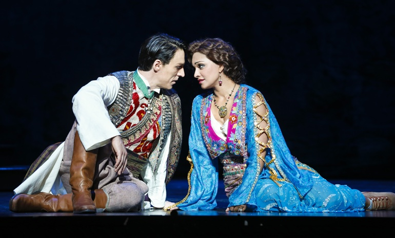 A man and woman in exotic dress kneel on stage and look into each other's eyes.