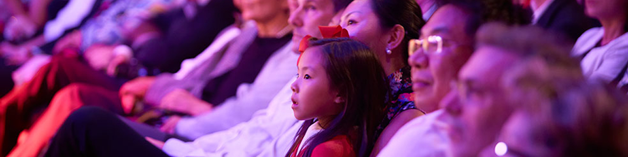 A child sits in her mother's lap at the opera, gazing happily up at the stage