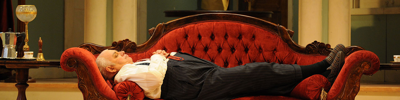 Don Pasquale lies down on a sofa to rest
