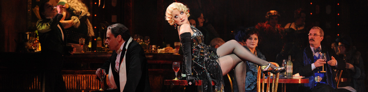 Taryn Fiebig as Musetta in La Boheme, wears a cocktail dress and reclines on a table.