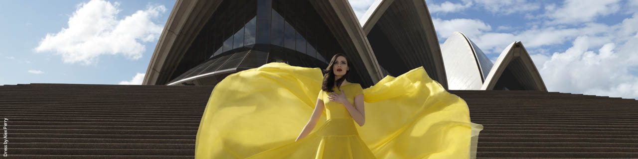 An opera singer wears a yellow dress on the steps of Sydney Opera House