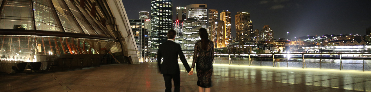 A young couple walks towards the Sydney skyline outside Sydney Opera House
