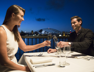 A young couple toasts sparkling wine at the Platinum Club at Handa Opera on Sydney Harbour with Sydney Opera House in the background