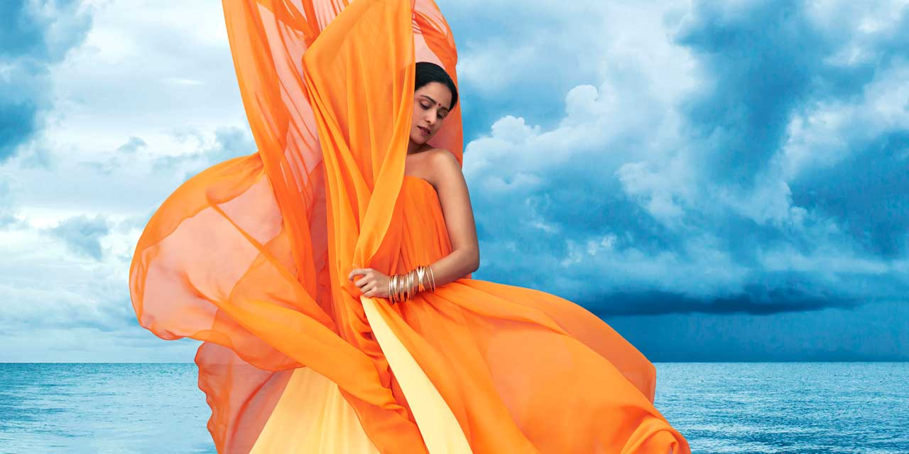 Stacey Alleaume, soprano, stands in front of a stormy sky with orange fabric billowing around her