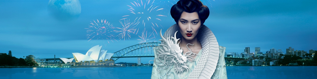 Turandot stands in front of Sydney Harbour with a dragon curled around her neck