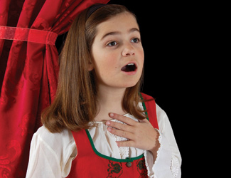 A young girl singing with her hand on her heart standing in front of a red curtain