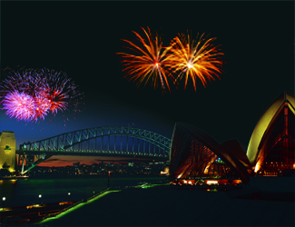 The Sydney Opera House and Harbour Bridge at night with a firework going off between them.