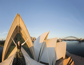 Lorina Gore at first light stands on top of the Opera House sails