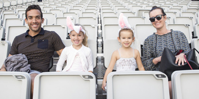 A family of four pose for a photo in the empty grandstand at Handa Opera on Sydney Harbour