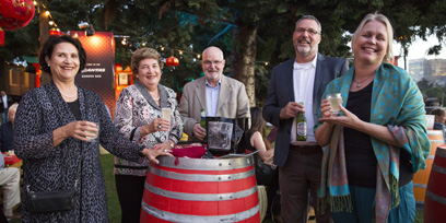 Three women and two men stand around a red laquered barrel holding drinks and smiling