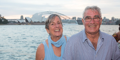 A laughing couple sit at the edge of Sydney Harbour in front of the Sydney Opera House and Harbour Bridge