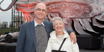 A man poses with his arm around a woman, both smiling, in front of the dragon at Handa Opera on Sydney Harbour