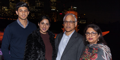 A family of four pose for a photo in front of the Handa Opera on Sydney Harbour stage