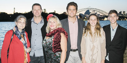A family of six pose for a photo in front of Sydney Harbour