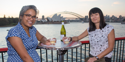 Two women sit and pose for a photo at Opera on the Harbour