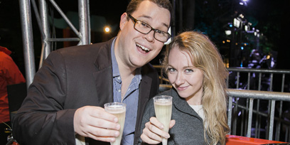 A man and a woman hold their champagne glasses up to the camera