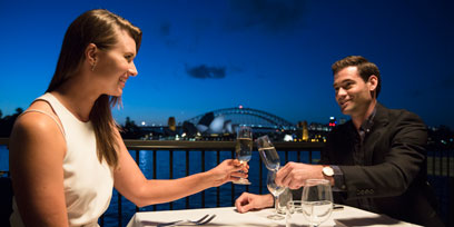 A couple drink sparkling wine in The Platinum Club against the backdrop of Sydney Harbour