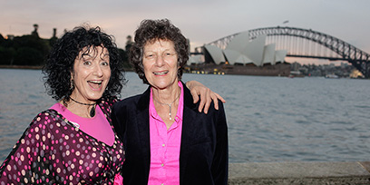 Two women in pink pose in front of the Sydney Opera House and Harbour Bridge