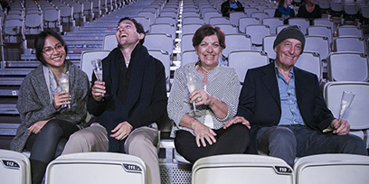 A laughing family of four sit in an empty grandstand