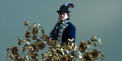 Diego Torre in period costume standing behind some brass roses