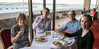 A family raise a glass at a table in the Northern Foyer bar at Sydney Opera House