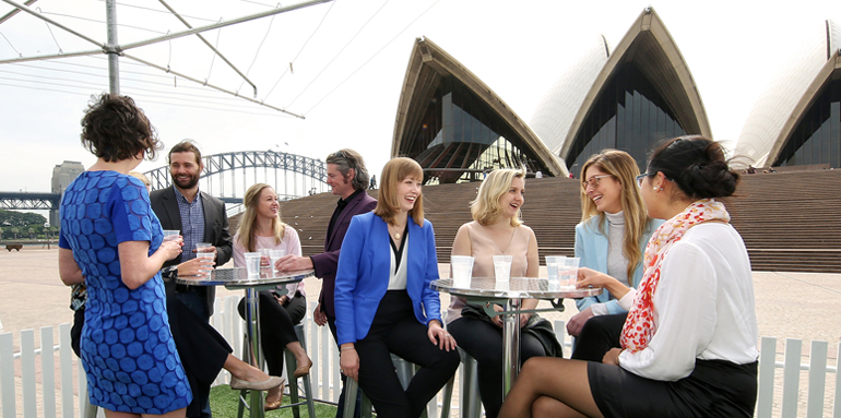 A group of people sitting at          bar tables on in front of the Sydney Opera House talking and laughing.
