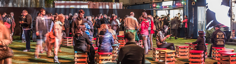 Groups of people sit at bar tables while a crowd mingles in the background.