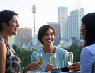 Three women smiling with drinks in their hand and Centre Point Tower in the background