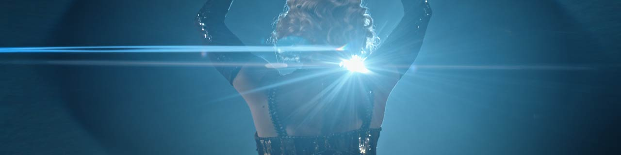 a backlit singer dressed in a 20's style flapper dress