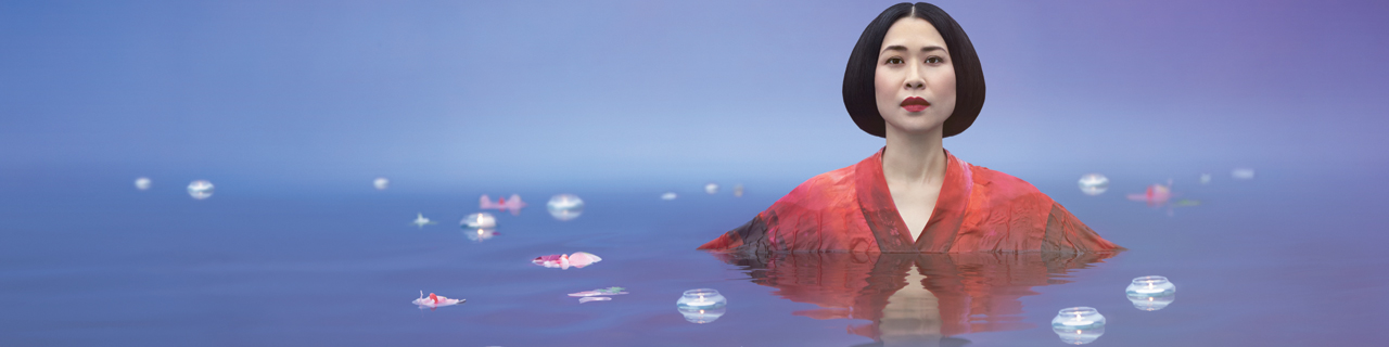 Hyeseoung Kwon stares at the camera, dressed in kimono surrounded by water and petals