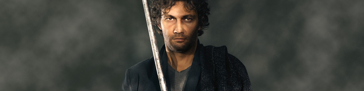 Tenor Jonas Kaufmann, draped in a black robe, and holding a staff, looks directly into the camera.