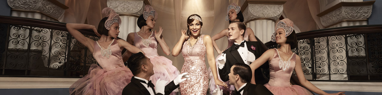 Danielle de Niese in The Merry Widow with gentlemen and ladies surrounding her