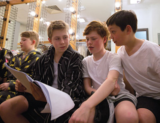 Three boys sit in a dressing room and look over a score of The Marriage of Figaro