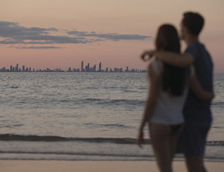 A couple walk along a beach at sunset, with the Gold Coast skyline in the background.