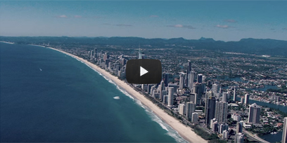 An aerial photo of the Gold Coast with a transparent play button overlaid