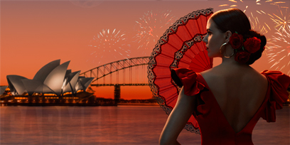 Sian Pendry is Carmen in a stunning red dress, holding a lace fan, against the backdrop of Sydney Harbour, as fireworks explode across the night sky over Sydney Opera House & the Sydney Harbour Bridge.