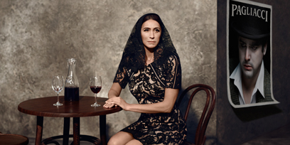 Dragana Radakovic sits at a table in a black lace dress, with two glasses and a carafe of wine in front of her.