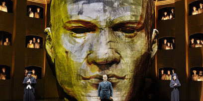 A giant head sits in the middle of the set for King Roger, and a man in a suit stands in front of it.