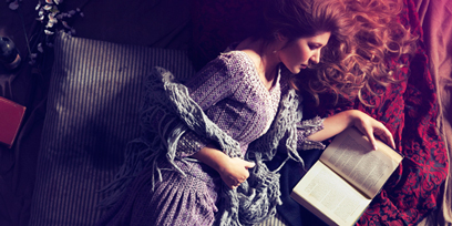 Soprano Nicole Car lays on a dirty mattress, her long hair spread around her, reading a book.