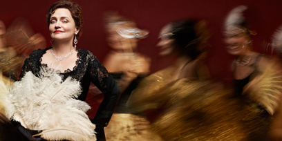 Soprano Emma Matthews as Violetta: she wears an opulent black dress, long black gloves, and holds a white feathered fan. A blur of party-goers dance behind her.