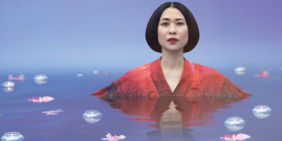 Soprano Hyseoung Kwon wears a kimono, submerged in a pond. Candles and lilies float on the water.