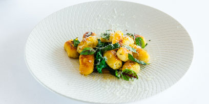 golden gnocchi with greens and shaved parmesean
