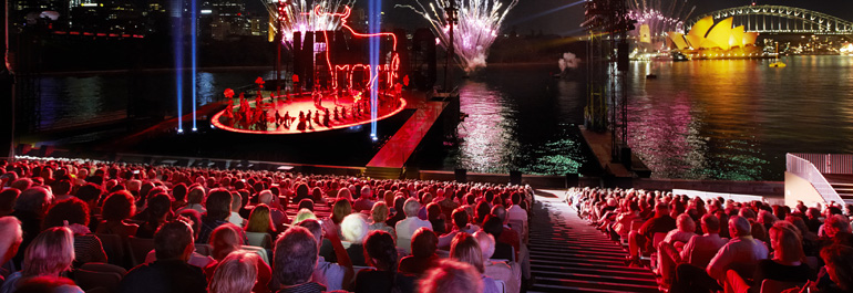 The audience sits in the grandstand at Handa Opera on Sydney Harbour and looks at the floating stage.
