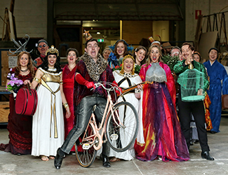 Opera Australia performers in costume, with a man on a bicycle at the front of the group.
