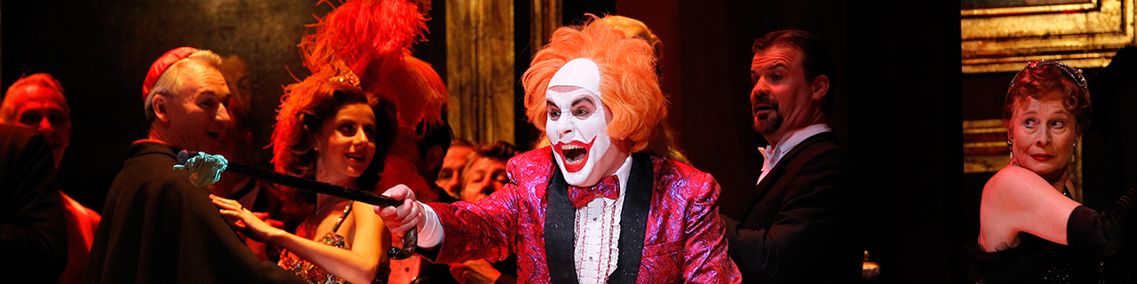 A man in clown makeup points at the audience
