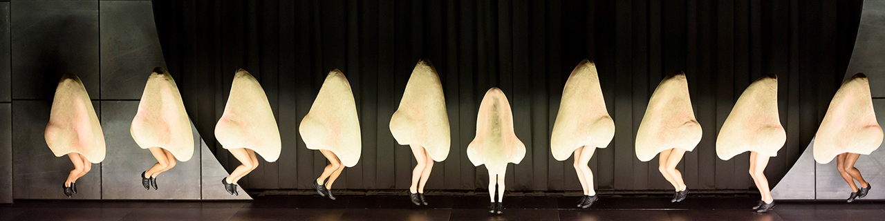 A chorus line of dancers dressed in giant noses
