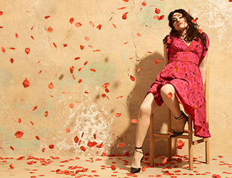 woman sitting on a stool in a shower of rose petals