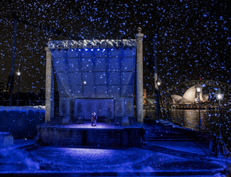 Snow falls as a couple embraces in the production of La Boheme.