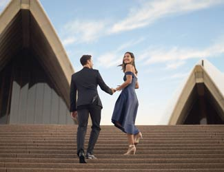 Couple walking up the steps of the Sydney Opera House to attend the opera.