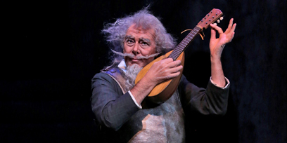 An old man tunes a lute
